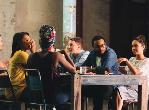 A group of young people discussing around a table